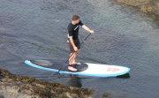 SUP paddler on a rocky coast