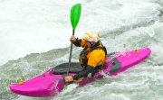 White water paddler in bright pink kayak