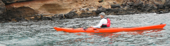 sea kayaker in front of cliffs