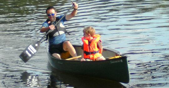 family paddling in open canoe