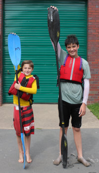 Boys of different heights with kayak paddles of different length