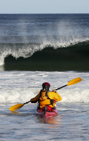Sea Kayaker heads out through surf