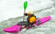 White water paddler in bright pink kayak